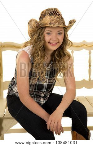 A woman with down syndrome in her western hat and clothing sitting on a bench with a smile.