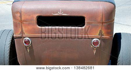 Custom vintage retro unpainted car displayed outdoors.