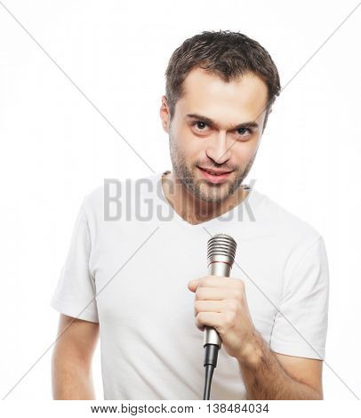 Life style, people and leasure concept: a young man wearing a white shirt holding a microphone and singing. Isolated on white.
