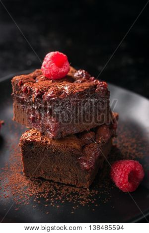 Homemade chocolate sweet brownies cakes with cherry and raspberries on a dark background closeup
