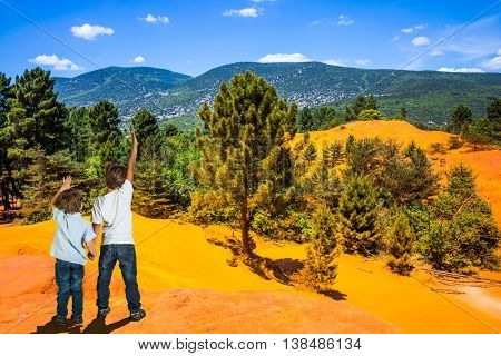 Orange and red picturesque hills in Languedoc - Roussillon, Provence. Two boys - brothers of seven and four years admire the magnificent nature
