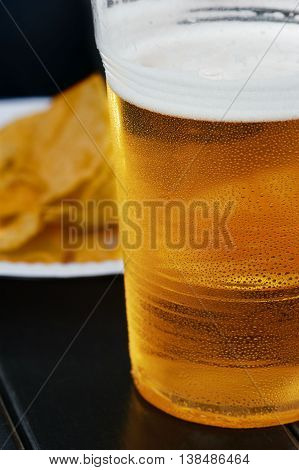 Glasses of light beer and potato chips