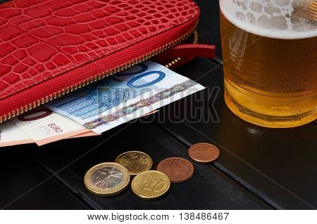 Glass of beer red wallet with euro and coins
