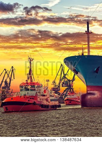 Tugs towing cargo ship in port of Gdansk Poland.
