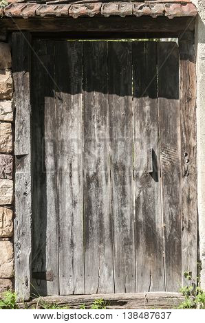Old wooden vintage door on stonewall fence of country house