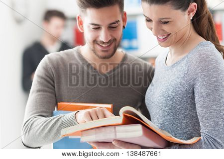 Smiling schoolmates holding books and studying together in the school library learning and education concept