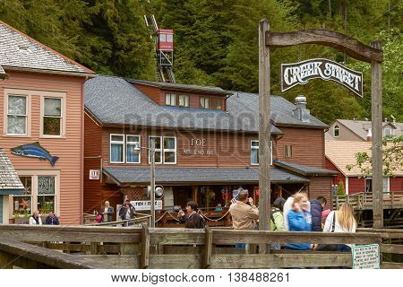 KETCHIKAN ALASKA USA - MAY 29 2011: People Looking for Salmon and Photographing while Enjoying Visit of Creek Street in Ketchikan Alaska.