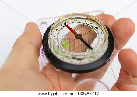 Detail Of Hand Holding Glass Compass On White Background