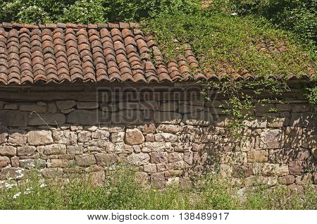 Wall of old stone farmhouse with tiled roof
