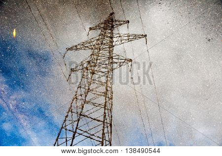 electric tower reflection on a water puddle with blue sky