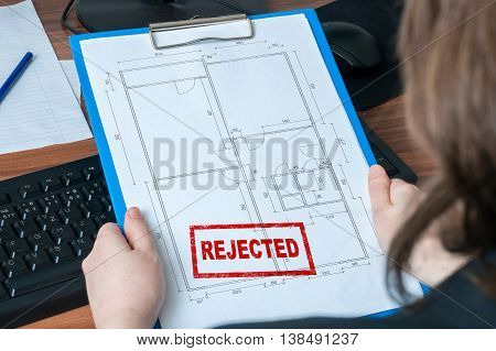 Business Woman Holds Architectural Drawing (blueprint) With Reje
