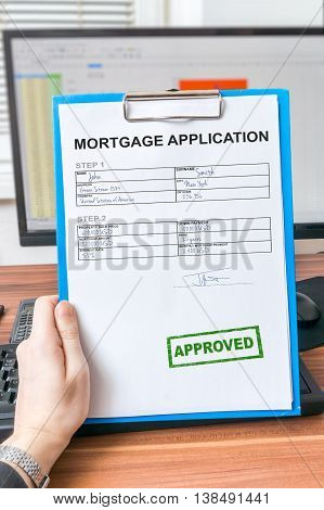 Hand is holding mortgage application with approved stamp.
