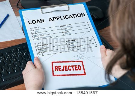 Business woman is holding loan application with rejected stamp.