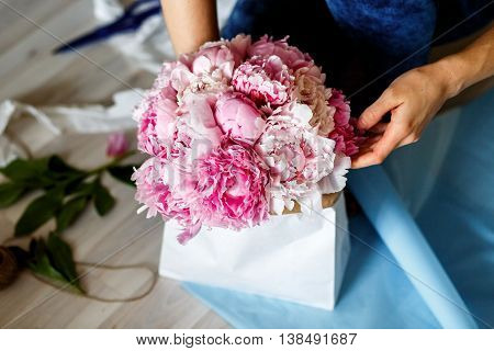 Florist making a bouguet of peonies in kraft paper bag - workshop