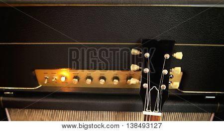 Electric Guitar leaning against an amplifier with control panel and knobs and toggle switches - power light glowing