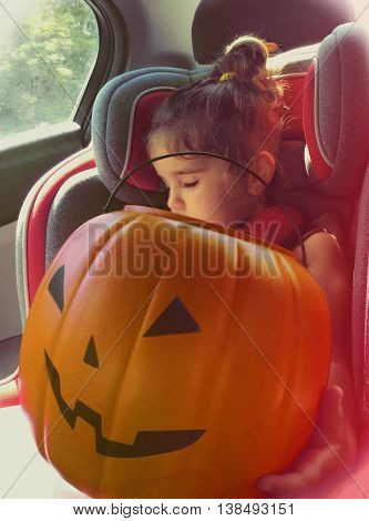 Young girl asleep in a car seat holding a plastic halloween pumpkin jack o lantern