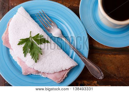 Casabe (bammy beiju bob biju) - flatbread of cassava (tapioca) with ham and parsley on wooden background. Selective focus