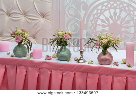 Flowers and candles on a celebratory table. Wedding decorations