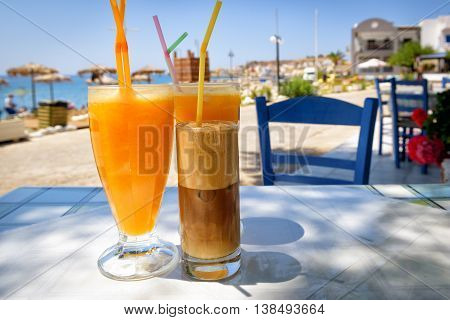 Glasses with orange juice and greek coffee frappe