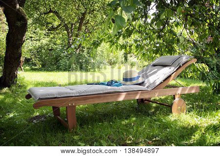 garden daybed made of wood with a summer hat on a sunny meadow in the orchard, enjoy leisure