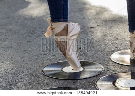Foot girl in Ballet shoes stands against the backdrop of vinyl discs that lie on the road.