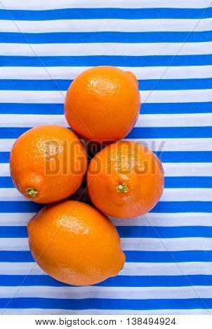 Fresh citrus fruits on a light striped background