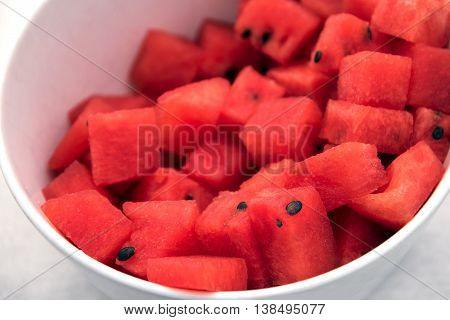 red watermelon slices in a white bowl fresh cool snack in the summer closeup with selected focus and narrow depth of field