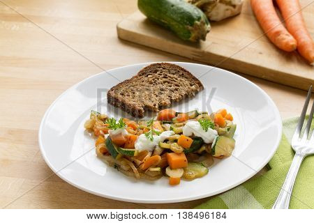 fresh vegetables from zucchini carrots and celery with soured cream parsley garnish and whole grain bread on a wooden kitchen board a light and healthy vegetarian meal with low calories selected focus and narrow depth of field