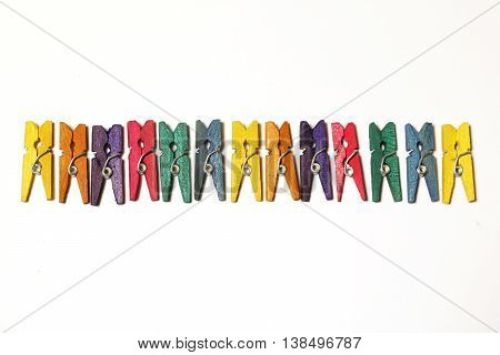 Colourful mini clothes pegs on white background