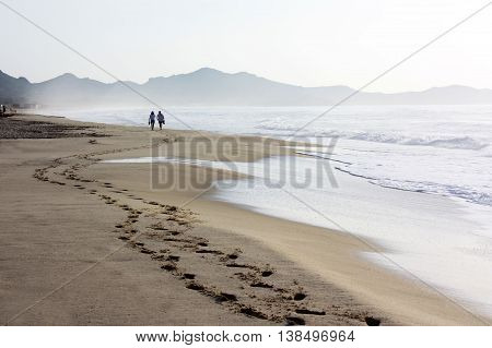 A famous beach Costa Rei with a walking couple along it in a cloudy day. Location Sardinia Italy.