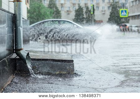 Rain water flowing from metal drainpipe during a flood. splashes of cars background. concept of protection against heavy downpours
