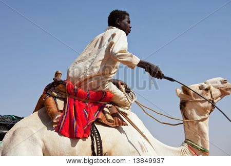 SUDAN - JANUARY 09: Sudanese boy riding a camel near Nubian pyramids on January 9, 2010 in Sudan. Young camel riders are common at touristic objects offering a camel ride or guide service for a penny.