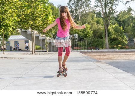 outdoor portrait of young smiling teenager girl riding skateboard, urban background