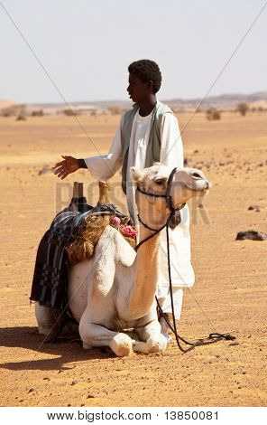 SUDAN - JANUARY 09: Sudanese man riding a camel near Nubian pyramids on January 9, 2010 in Sudan. Young camel riders are common at touristic objects offering a camel ride or guide service for a penny
