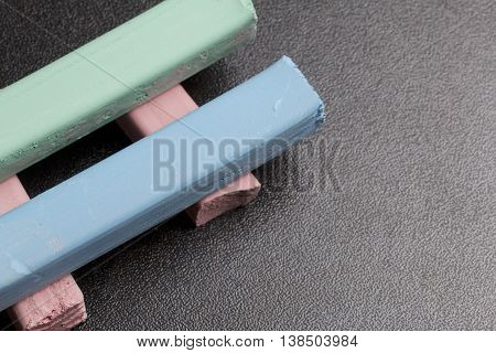 Chalk for drawing. Multi-colored chalk. Different colors. Blue and lime lying on the pink.