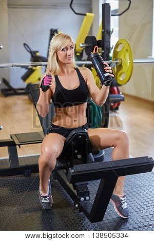 The sports young woman with a protein cocktail in a shaker sits in a gym. Sports nutrition.