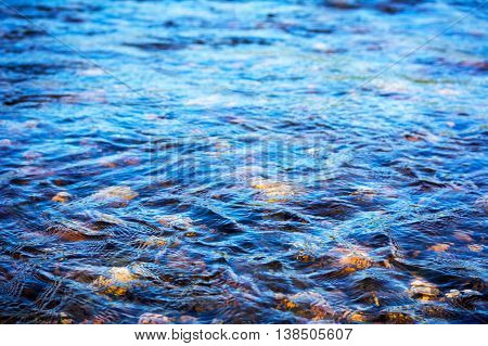 Defocused blue water surface background. Stony bottom of a clear mountain river. Flecks of sunlight and ripples on the water of river. Water background. Water surface texture.