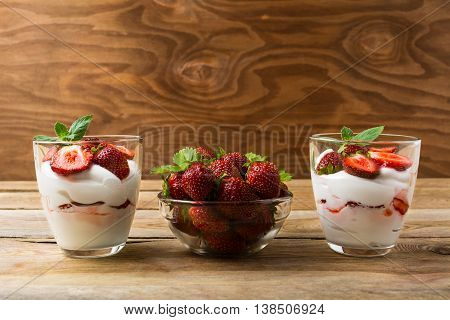 Strawberries dessert with whipped cream on rustic wooden background. Cream cheese layers and ripe strawberry.