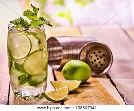 Alcohol drink. On wooden boards three glasses with alcohol drink and ice cubes. Drink hundred fifty five cocktail mohito with cocktail metal shaker and mint . Country still life. Light background.