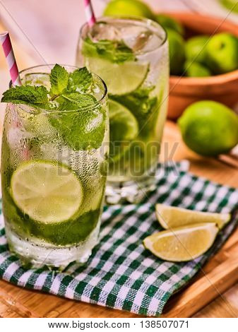 Alcohol drink. On wooden boards two glasses with alcohol drink and ice cubes. Drink hundred sixty three cocktail mohito with straw and lime and mint on checkered cloth. Country life. Light background.