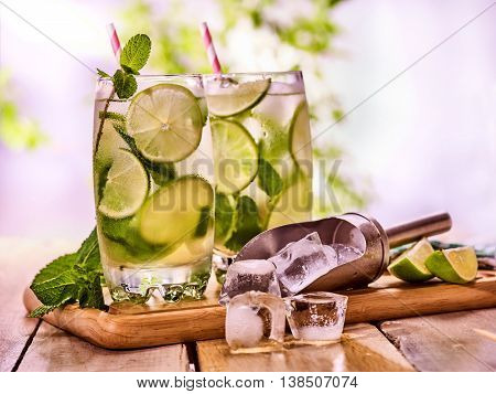 Alcohol drink. On wooden boards two glasses with alcohol drink and ice cubes. A drink number hundred fifty eight cocktail mohito and scoop ice with straw. Country still life outdoor. Light background.