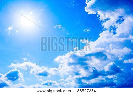 Cear blue sky with fluffy clouds and sunbeams. Beautiful cloudy blue sky background