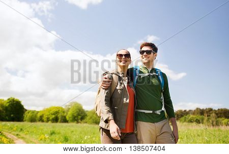 travel, hiking, backpacking, tourism and people concept - happy couple with backpacks hugging and walking outdoors
