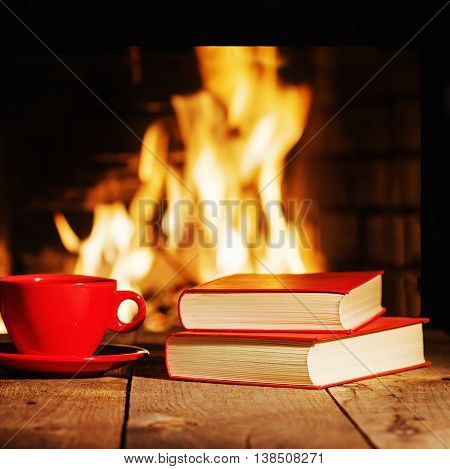 Red Cup Of Tea Or Coffee And Old Books Near Fireplace..