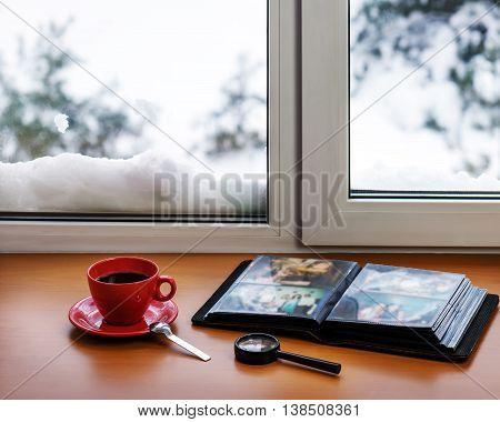 Red Cup Of Coffee Or Tea With A Metal Spoon, Photo Album And Loupe.