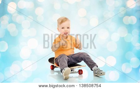 childhood, sport, leisure, gesture and people concept - happy little boy sitting on skateboard and showing thumbs up over blue holidays lights background