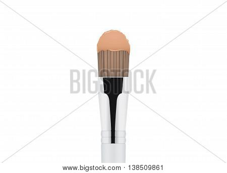 Foundation cream brown color on cosmetic brush.