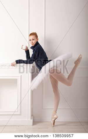 Pretty young ballerina standing by the fireplace drinking tea. A girl wearing a tutu and black sweater.