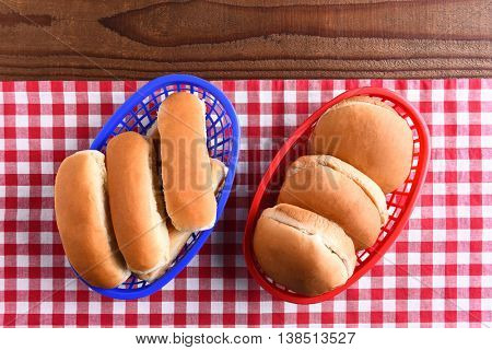 Hamburger and hot dog buns in plastic baskets on a picnic table . the red white and blue themed image is fit for patriotic holiday themes.