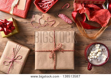 High angle view of Christmas presents and hot chocolate on a wood table. Plain wrapped gifts with string, candy canes and ribbon.